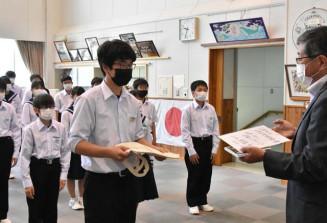 高橋嘉行理事長(右)からサイン色紙を受ける前川学さん