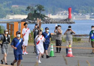 大槌湾の蓬莱島を背に、トーチを掲げて走る聖火ランナー。聖火リレーは東日本大震災の津波で被災した沿岸でつながれた=17日、大槌町赤浜