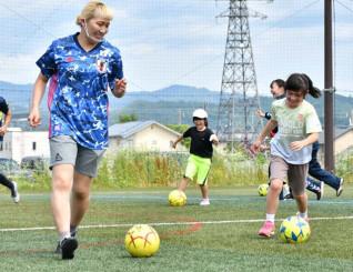 サッカー教室で、丸山桂里奈さん(左)とドリブルの練習をする子どもたち