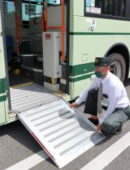 京都市バスに備え付けられたスロープを下ろす職員。スロープの形はバスによってさまざまという=同市南区・市交通局九条営業所