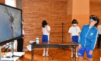 専用ゴーグルを着用し、陸前高田市の「奇跡の一本松」を見上げる生徒