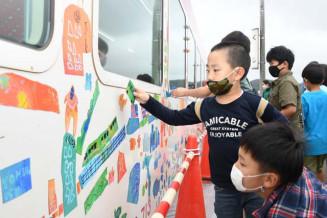絵を描いたマグネットを三陸鉄道の車両に張る子どもたち