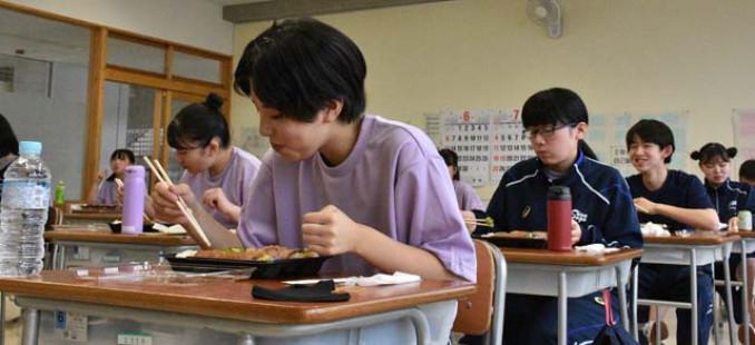 町内の飲食店から仕入れた弁当を食べる生徒
