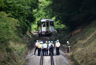倒木に衝突し、車両が脱線したJR大船渡線の現場を調べる鉄道事故調査官ら=6日午後3時15分、一関市滝沢
