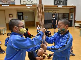 小林陵侑選手が聖火を運んだトーチの受け渡しを体験する柏台小の児童