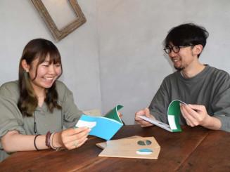 小冊子の「ひろのの栞」を笑顔で手にする大原圭太郎代表理事(右)