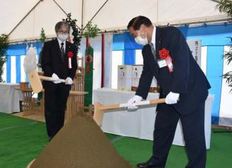 くわ入れをする谷藤裕明市長(右)と佐藤光彦社長