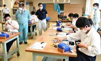 指導を受けながら技能試験の練習に励む生徒