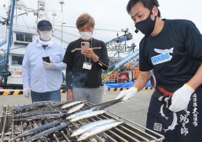 佐藤正光師範代(右)の指導を受けながらサンマの炭火焼きに挑戦する参加者