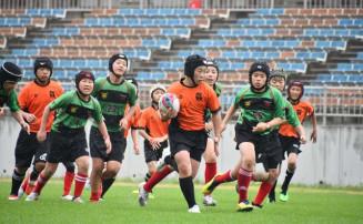 天然芝のピッチで全力プレーを見せる子どもたち=10日、釜石市・釜石鵜住居復興スタジアム