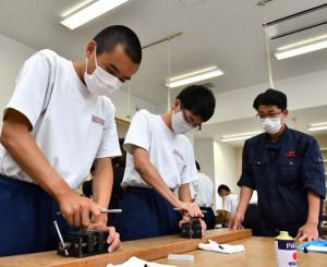 福岡工高の生徒(右)の指導を受け、文鎮作りに取り組む福岡中の生徒