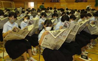 新聞に目を通しながら、構成の工夫などに理解を深める見前中の生徒ら