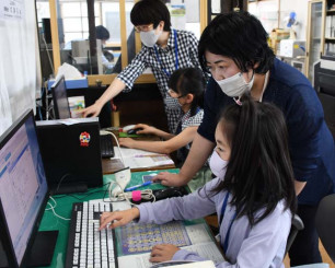 図書館司書の業務を体験する児童ら