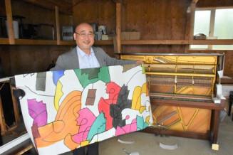 小林覚さんがデザインしたピアノにラッピングするシートを持つ鹿討康弘さん