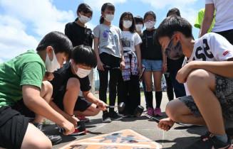 ゴムハンマーを使い路面標示を貼り付ける東和小6年生