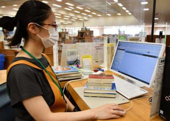新たに導入したIC機器の運用方法を確認する中央図書館の職員