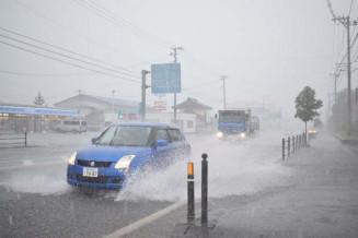 短時間に強い雨が降った遠野市内。水しぶきを上げ慎重に車が走った=21日午後1時11分、同市松崎町