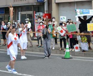 東京五輪聖火リレーでトーチを掲げる小野寺ひろ子さん(左)。見ている全ての人に難病患者への理解を訴えた=6月18日、一関市