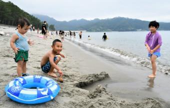 砂浜で遊びながら笑顔を見せる子ども