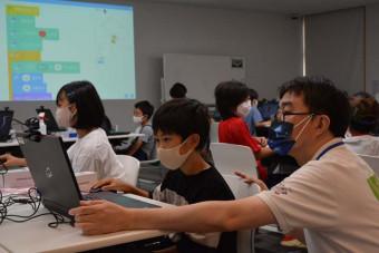 真剣な表情でプログラミングに挑戦する児童ら