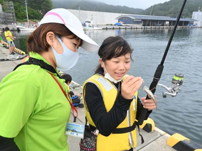 海釣り体験で魚を釣り上げた児童
