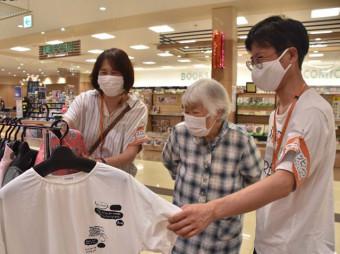 付き添いのパートナーと会話しながら買い物を楽しむ高齢女性(中央)