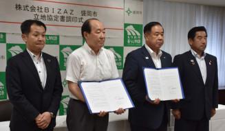 谷藤裕明市長と立地協定書を交わす坂本一彦代表取締役(左から2人目)