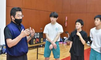 矢巾中の男子バスケットボール部員に助言する田村敏実さん(左)。部活動指導員の拡充など現場の改革が進む=矢巾町