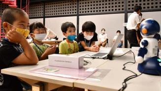 ロボットの言動を設定しながら、プログラミングを楽しく学ぶ子どもたち
