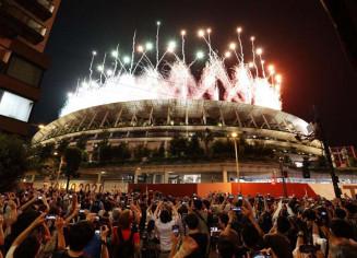 東京五輪の閉会式で国立競技場から打ち上げられたフィナーレの花火を路上で見上げる大勢の人たち=8日夜