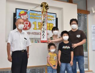 1万人達成を祝う斉藤俊明会長(左)と家族
