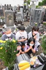 盆の入りを迎え、墓前で手を合わせる家族連れ=13日、盛岡市仙北・長松寺