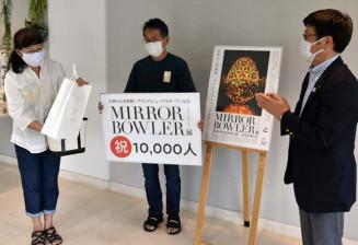 佐々木光司町長(右)から1万人記念のプレゼントを受け取る吉田泰次さん(中央)、美和子さん夫妻