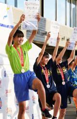 陸上女子走り高跳びで県勢初の優勝を遂げ、踏み切りのポーズで賞状を掲げる高橋美月(左)=19日、茨城県ひたちなか市・笠松運動公園陸上競技場