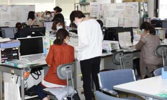 慌ただしく業務に当たる盛岡市保健所の職員。新型コロナウイルスの感染が急拡大し、保健所や医療機関の負荷が増している=同市神明町
