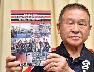 写真集を手に「悲惨な震災の記憶を風化させることなく、次代につなげたい」と語る山下修治団長
