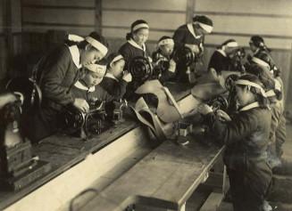 鉢巻き姿でミシンを手入れする秋元浅子さん(左から3人目)ら