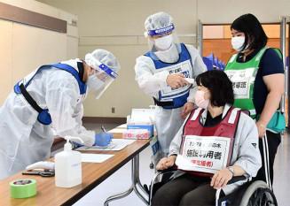 避難所の受付で検温する町職員=4日、西和賀町・湯田農業者トレーニングセンター
