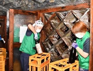 龍泉洞内の貯蔵庫で熟成させた日本酒を取り出す従業員ら