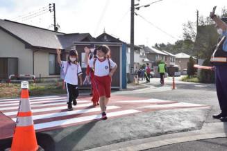 ハンプ設置で10センチ高くなった横断歩道を渡る滝沢中央小児童