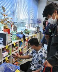 野菜や缶詰など食品を熱心に品定めする外国人留学生