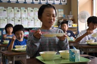 「九戸うまみたっぷり給食」を味わい笑顔を見せる伊保内小3年生