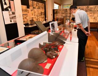 ヘルメットやレコードなどが並び、戦争の悲惨さを訴える企画展