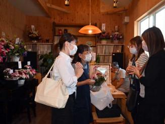 お祝いの花であふれる店内で客を迎える照井由紀子店主(左から2番目)