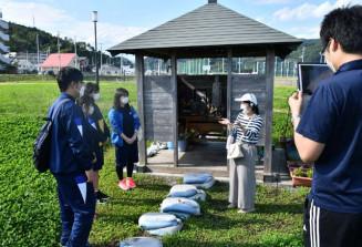 高木桜子さん(右から2人目)から震災前のまちの様子などを聞く生徒ら。撮影した動画は映像としてまとめる