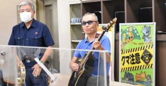 クマ被害防止を呼び掛ける楽曲を披露する田口友善さん(右)と作詞作曲の登堂かほるさん