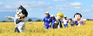 収穫間近の田んぼで、自分たちが製作したかかしを見る矢巾東小の児童