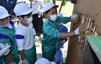 漆室の土壁を塗る安代小の児童