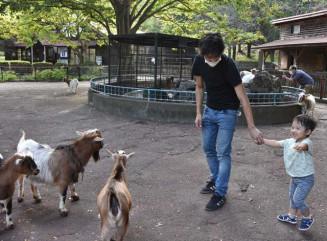 リニューアル前最後の開園日に動物と触れ合う親子連れ