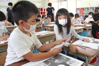 さまざまな生き物の生態を読み取る児童ら